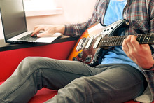 Casually Dressed Young Man With Guitar Playing Songs In The Room At Home. Online Guitar Lessons Concept. Male Guitarist Practicing Chord Grips.