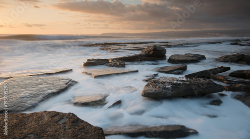 Rocky seashore seascape with wavy ocean during sunset
