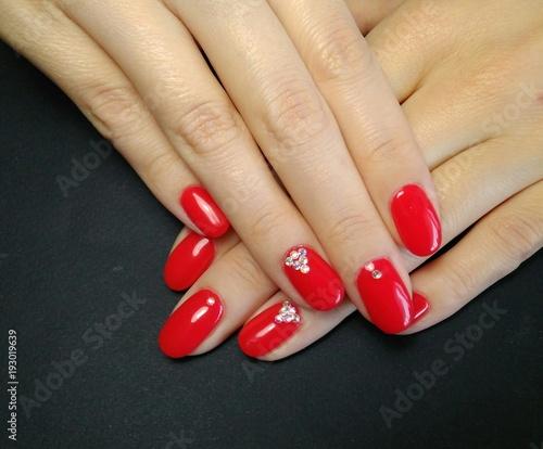 Elegant manicure. Red gel nail polish with rhinestones on a black ...