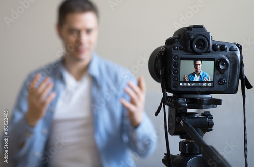 Obraz Handsome man making video blog. Focus on camera. - fototapety do salonu
