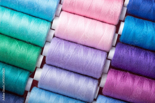 Photo  sewing thread in different colors pink blue green red