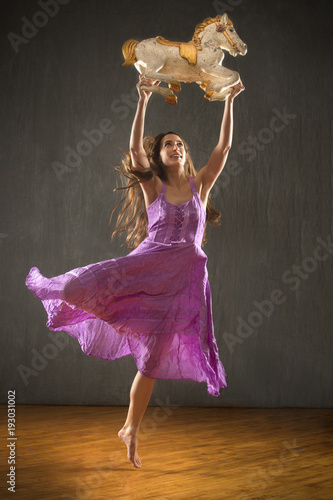 Fotografie, Obraz  Young woman in purple dress dancing with antique carousel horse.