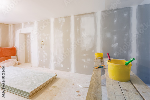 Fotografía  Putty knife, yellow buckets with glue and glue rollers on the wooden board in room  is under construction, remodeling, renovation, extension, restoration and reconstruction