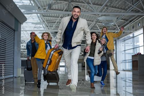 Happy men and women with cases hurrying up for boarding Billede på lærred