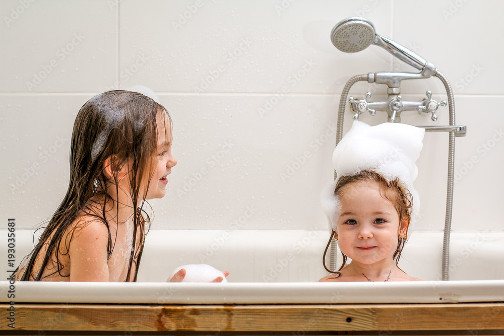 Fototapeta Two little sisters play in a bath.