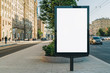 canvas print picture Vertical blank glowing billboard on the city street. In the background buildings and road with cars. Mock up. The poster on the street next to the roadway.