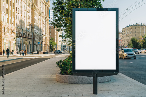 Fotobehang Historisch geb. Vertical blank glowing billboard on the city street. In the background buildings and road with cars. Mock up. The poster on the street next to the roadway.