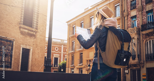 Sunny day. Back view. A young tourist woman in a hat and with a backpack is standing on a city street and is looking for a way on the map. A girl traveler walks the city, looks at the sights.