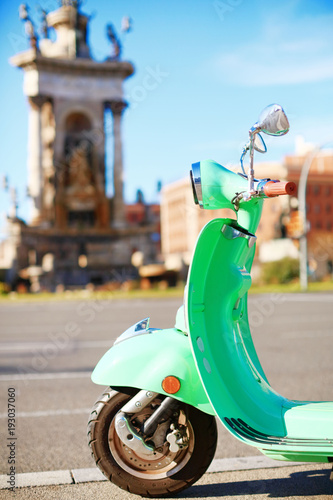 Poster Scooter Vintage bright green scooter parked on the street of Barcelona on a sunny day