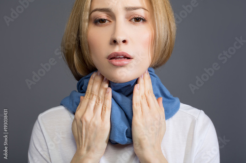Cuadros en Lienzo Portrait of sick sad woman in scarf wrapped around her neck, she is touching her throat and looking at camera