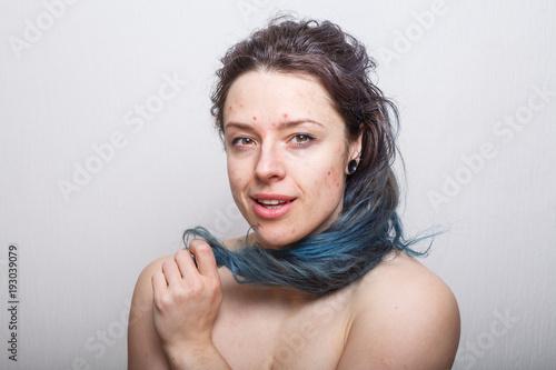 Young woman rolling her colorful but damaged messy hair on her finger Wallpaper Mural