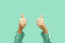 Thumbs Up, Two Hands. View Of Two Hands With Raised Thumbs, Isolated On A Green Pastel Background. Everything Is Fine, Good News, Good Information.
