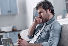 Bad Thoughts. Depressed Unshaved Divorced Man Sitting Alone In His Little Flat With His Hand Touching His Face And Thinking About His Miserable Condition While Drinking Alcohol