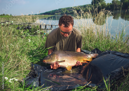Photo Happy angler with carp fishing trophy