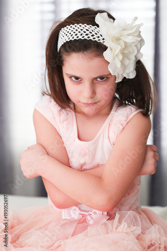 30a393bdcf44 6 or 7 Years Old Little girl with Dark Hair and Brown Eyes, with White  Flower Headband,Funny Expression, sad, angry, posing isolated on blurry  background