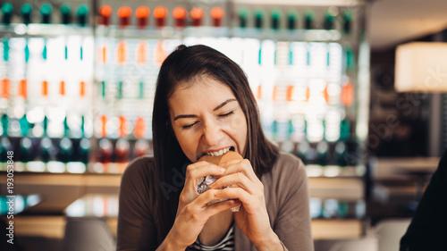 Fotografie, Obraz  Young woman eating fatty hamburger