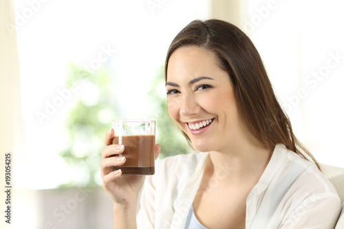Girl holding a cocoa shake looking at you