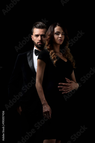 elegant man and woman posing next to each other on studio.