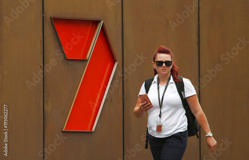 A woman walks in front of the Channel 7 logo in Sydney - Buy this