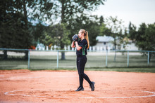 A Teenage Girl Holding Glove Up To Her Face With Long Hair In A Ponytail Standing On The Pitchers Mound Ready To Pitch In A Black And Green Baseball Uniform