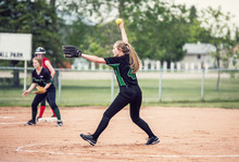 A Teenaged Girl In Baseball Pitching Motion On A Pitchers Mound With Long Hair In A Ponytail And Black And Green Ball Uniform