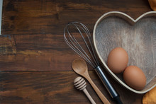 Kitchen Tools For Bakerry Or Cooking. Raw Eggs With Wooden Spooon, Orange Napkin, Heart Shape Box And Baking Tools. Copy Space. Flat Lay.