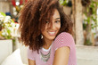 Half length portrait of beautiful attractive African American woman sits against cafe interior, has shining smile on face, being in high spirit after walk with boyfriend outdoor. Positive emotions