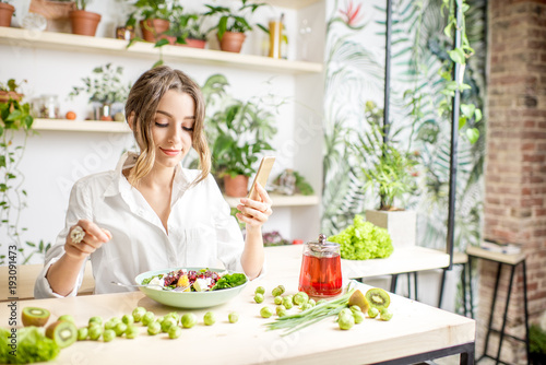 Deurstickers Kruidenierswinkel Young woman eating healthy food sitting in the beautiful interior with green flowers on the background