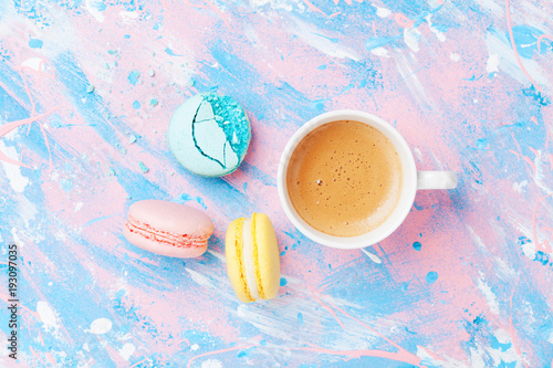 Cake macaron or macaroon and cup of coffee on colorful table top view. Flat lay style. Creative breakfast for Woman day. Punchy pastel.