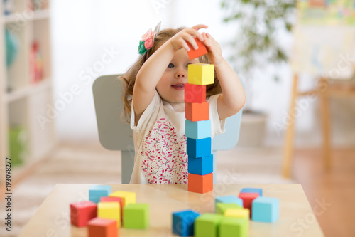 Kid girl playing with block toys in daycare center Canvas Print