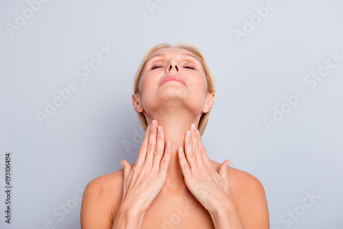 Portrait of pretty, charming, attractive woman enjoying her perfect skin holding Wallpaper Mural