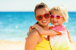 happy modern mother and daughter in colorful clothes on beach