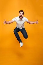 Full Length Portrait Of An Excited Bearded Man Jumping