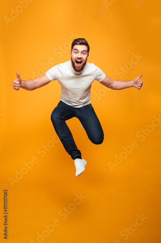 Full length portrait of an excited bearded man jumping Canvas Print