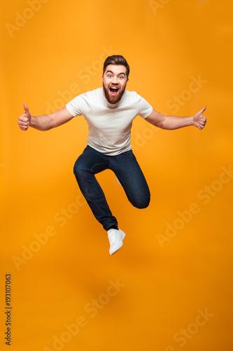 Fototapeta Full length portrait of an excited bearded man jumping