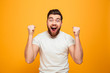 Leinwandbild Motiv Portrait of an excited bearded man celebrating success