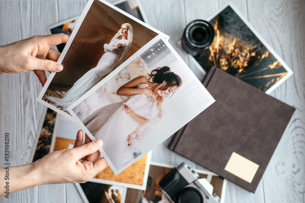 Fototapety, obrazy: Printed wedding photos with the bride and groom, a vintage black camera, photoalbum and woman hands with two photos