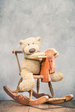 Teddy Bear Toy Sitting On Old Retro Wooden Rocking Horse Front Concrete Wall Background. Vintage Style Filtered Photo