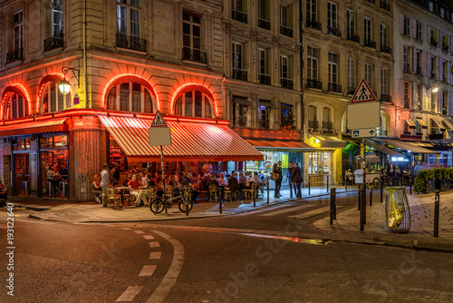 Obraz na plátně Cozy street with tables of cafe in Paris at night, France