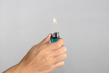 Hand Holds Blue Lighter In Hand And Pressing It. Isolated On White Background.