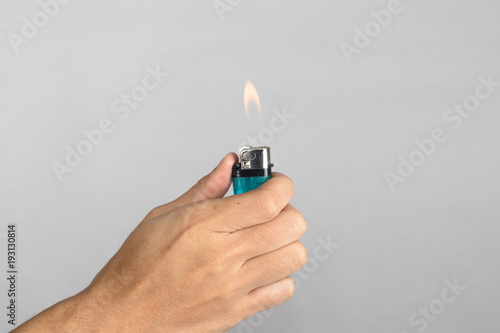 Hand holds blue lighter in hand and pressing it Canvas Print
