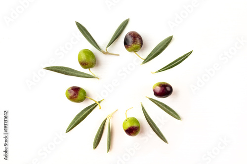 Olive leaves and olives forming frame on white with copyspace