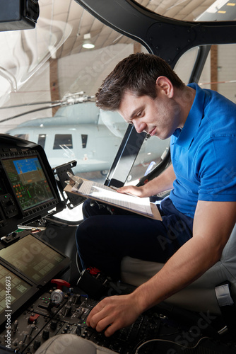 Male Aero Engineer With Clipboard Working In Helicopter Cockpit