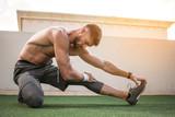 Muscular shirtless sportsman stretching legs before morning workout.