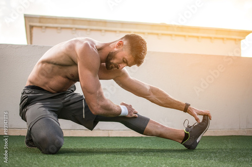 Fototapeta Muscular shirtless sportsman stretching legs before morning workout