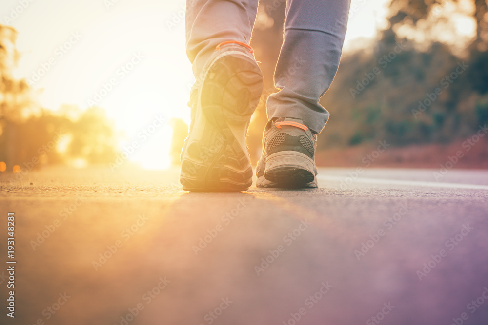 Fototapety, obrazy: man walking on road with sun light flare ,close up on shoe jogging workout wellness after work