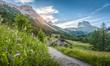 Leinwandbild Motiv Alpine scenery with mountain chalets at sunset in summer