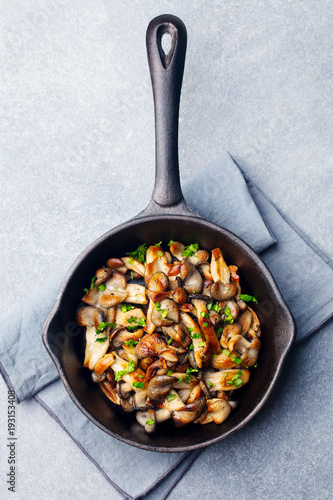 Fotografía  Fried mushrooms with fresh herbs in black cast iron pan. Top view
