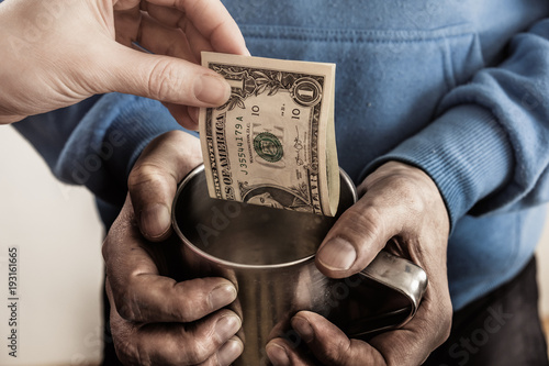 Photo Close-up hands with cup Dirty hands of a beggar homeless man and a dollar bill of alms