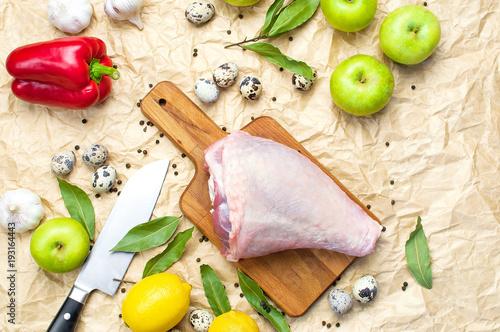 Fotomural Raw turkey thigh garlic apples lemon quail eggs spices on a wooden board